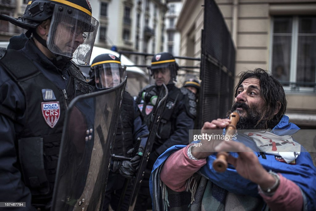 A man plays flute in front of riot police during a demonstration against the new LGV Lyon-Turin project, on December 3, 2012 in Lyon, on the sideline of the 30th France-Italy annual summit.