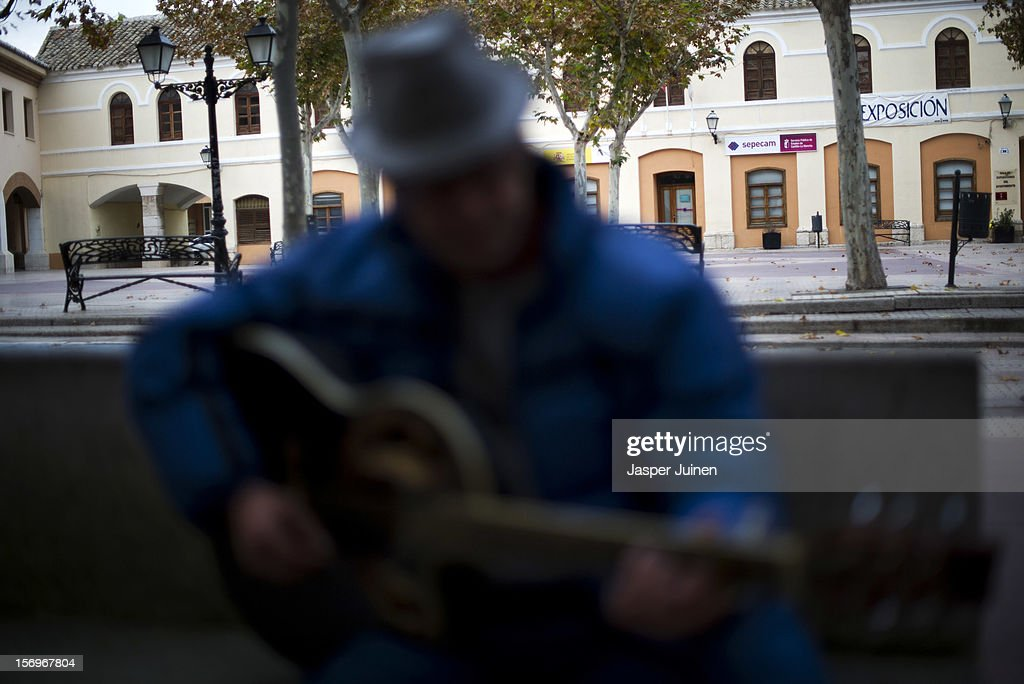 A man plays his guitar trying to make money on an empty Plaza Mayor on November 23, 2012 in Villacanas, Spain. During the boom years, where in its peak Spain built some 800,000 houses a year accompanied by the manufacturing of millions of wooden doors where needed, the people of Villacanas were part of Spain's middle class enjoying high wages and permanent jobs. During the construction boom years the majority of the doors used within these new developments were made in this small industrial town. Approximately seven million doors a year were once assembled here and the factory employed a workforce of almost 5700 people, but the town is now left almost desolate with the Villacanas industrial park now empty and redundant. With Spain in the grip of recession and the housing bubble burst, Villacanas is typical of many former buoyant industrial Spanish towns now struggling with huge unemployment problems.