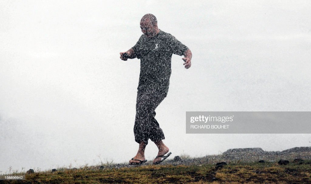 A man plays in the water as high waves hit the coastline on January 3, 2013 in Le Port, western part of French overseas' island of La Reunion, as cyclone Dumile approaches and authorities declare today a red alert that forbid people to leave their homes.