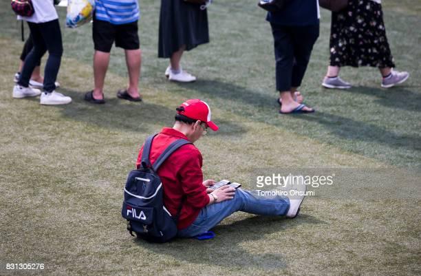 A man plays Nintendo Co's Pokemon Go augmented reality game on his smartphones during the Pokemon Go Stadium event at Yokohama Stadium that was held...