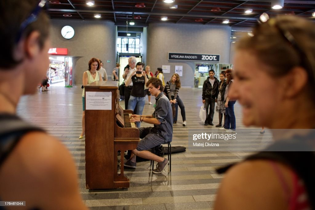 A man plays piano during the first day of the 'Pianos on the street' project at the main railway station on August 13, 2013 in Prague, Czech Republic. The project, by Prague cafe owner Ondrej Kobza, started in Prague today. Kobza placed pianos in five spots in the city centre for random passers-by to play. Similar projects run worldwide.