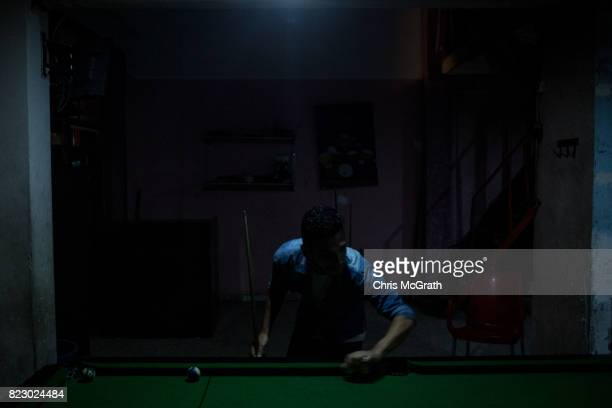 A man plays pool under minimal lighting at a pool hall in the AlShati refugee camp on July 21 2017 in Gaza City Gaza For the past ten years Gaza...