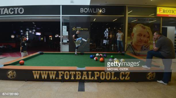 A man plays the ball during a footballpool match on April 28 2017 in Prague Footballpool is a combination of football and pool the sport uses...