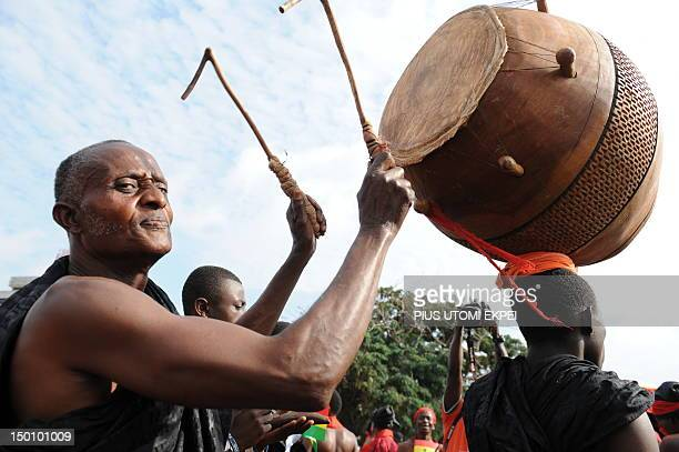 A man plays the drum as he gathers with other Ghanaian mourners to watch the casket carrying the remains of late Ghanaian President John Atta Mills...