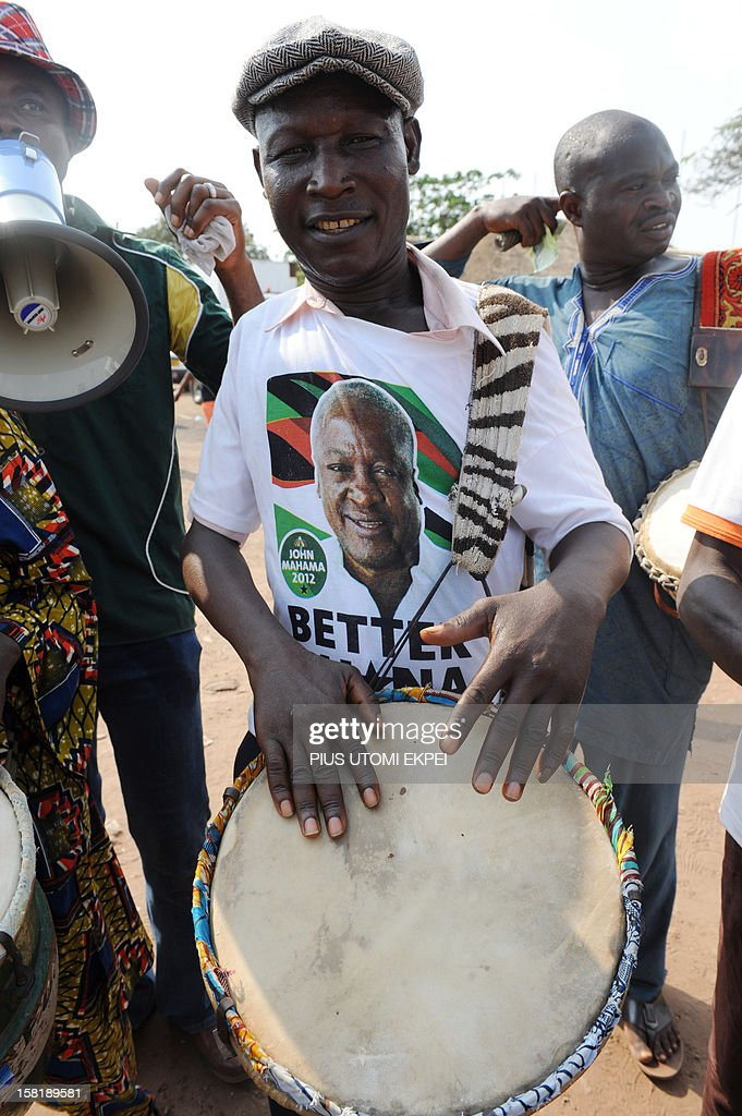 A man plays the drum to entertain Ghana's ruling National Democratic Congress party supporters gathered Kwame Nkrumah Circle in Accra on December 10...