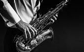 A man plays the saxophone close up.