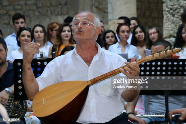 A man plays the saz during the Feast of Saints Peter and Paul at Batiayaz Armenian Church in Antakya Turkey on June 30 2017 An orchestra which...