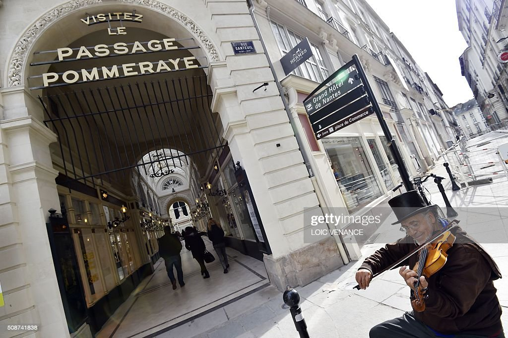 A man plays the violin in front of the entrance to the Passage Pommeraye shopping center in Nantes, western France, on February 6, 2016. / AFP / LOIC VENANCE
