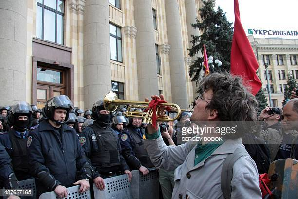 A man plays trumpet in front of policemen who guard the regional city building during a rally of proRussian protesters to mark the May Day in...