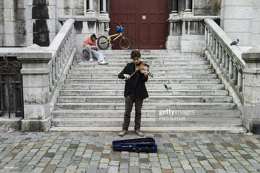A man plays violin at the Montmartre district, on September 22, 2013 in Paris.
