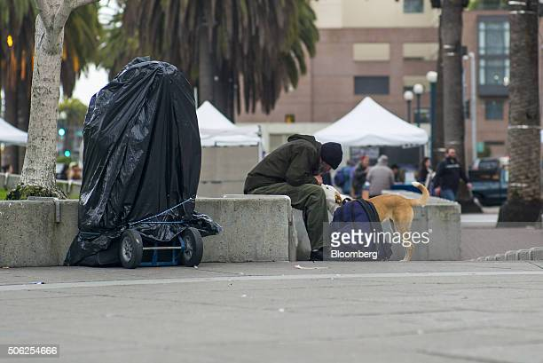 A man plays with a dog in Justin Herman Plaza in San Francisco California US on Thursday Jan 21 2016 San Francisco host city for the National...