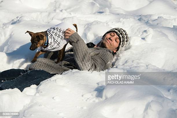 A man plays with his dog in the snow on Dupont Circle in Washington on January 24 2016 Millions of people in the eastern United States started...