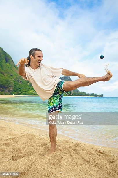 A Man Plays With His Hackey Sack In The Sand At The Water's Edge