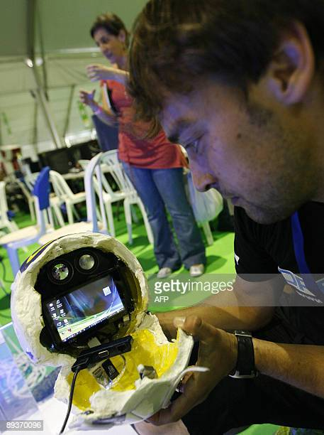 A man plays with his robot at Campus Party the world's biggest online electronic entertainment festival in Valencia on July 28 2009The meeting brings...