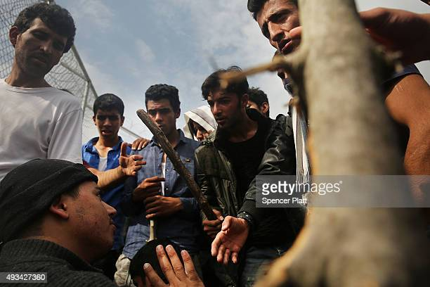 A man pleads not to be beaten as Afghan men with sticks fight with other recently arrived migrants waiting to be processed at the increasingly...