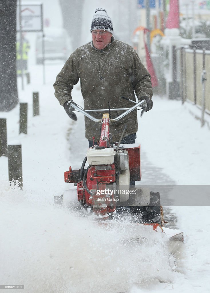 A man ploughs fresh snow from a sidewalk during a heavy snowfall on December 9, 2012 in Michendorf, Germany. Northeastern Germany was inundated with snow that covered highways and blanketed the region.
