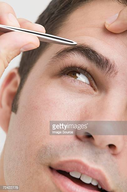 Man plucking his eyebrows