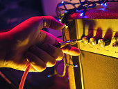 Man plugging jack into the guitar amplifier, closeup, for music, entertainment themes. Neon colorful light