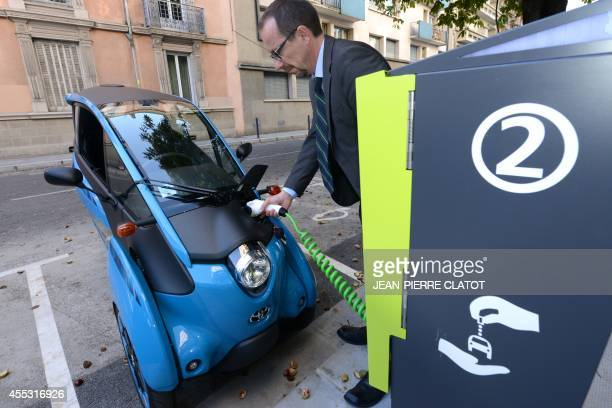 A man plugs his Toyota threewheeled electricpowered car named the IRoad on September 12 2014 in Grenoble during the presentation of a full electric...