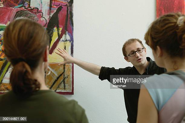 Man pointing at painting on wall in front of people