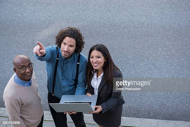 Man pointing explaining laptop work colleagues