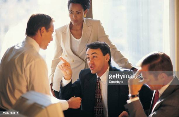 Man pointing finger at second man in meeting