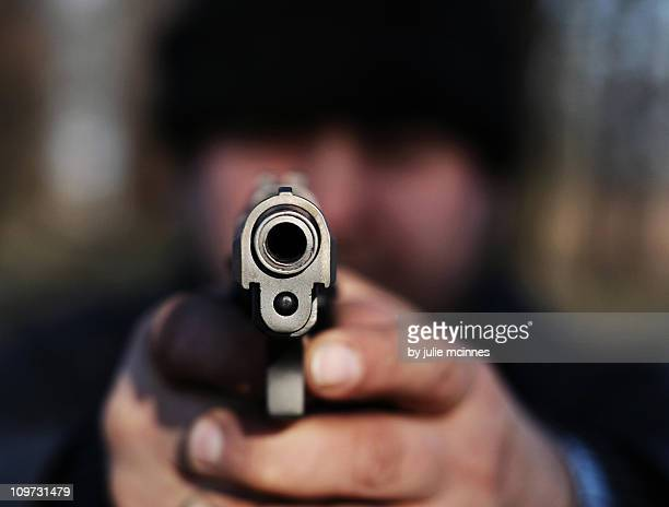 Man pointing gun directly at camera