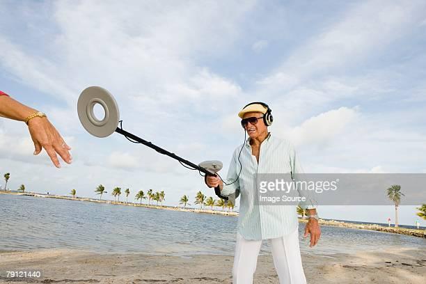 Uomo che indica metal detector in mano di donna