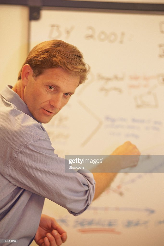 Man pointing to figures on board : Stock Photo