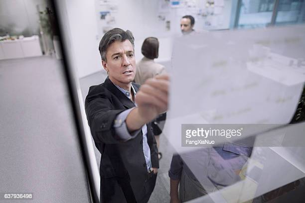 Man pointing to planning document on glass wall with coworkers