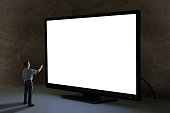 Man pointing tv remote control at world's biggest television that towers over him shining bright light in a dimly lit room with clean blank screen for your message and image sending a powerful message