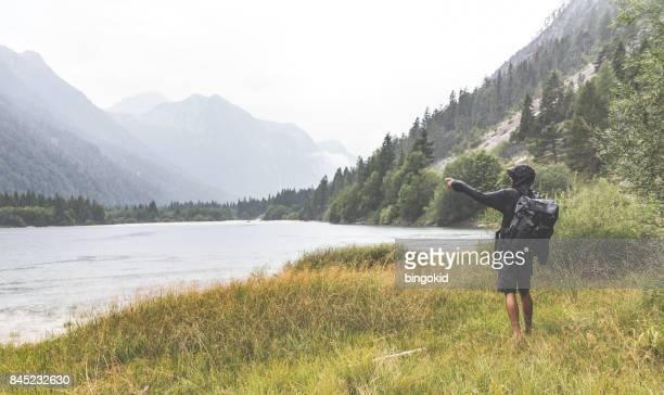 Mann zeigte mit der Hand in der Nähe des Sees im Regen