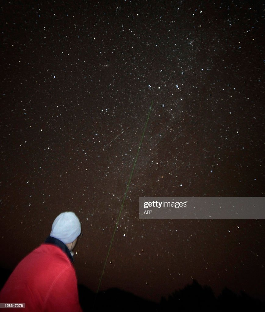 A man points a laser towards the Geminid meteor shower in the National Park of El Teide on the Spanish canary island of Tenerife on December 13, 2012.