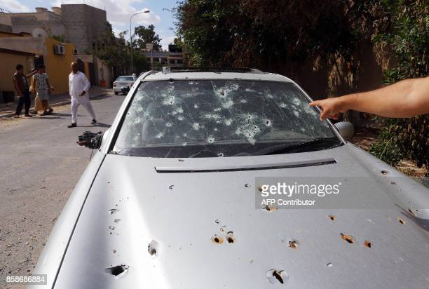 A man points at a bulletridden car in Sabratha on October 7 after three weeks of deadly fighting A security force loyal to Libya's internationally...