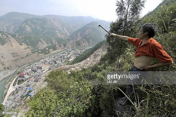 A man points at Tangjiashan lake which is holding 130 million cubic metres of water created when the quake triggered a landslide that blocked the...
