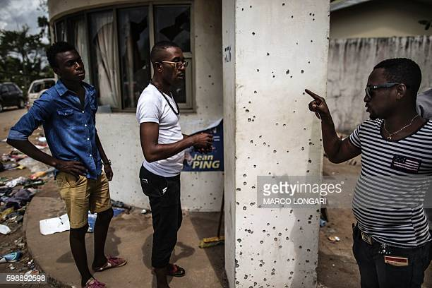 A man points out bullet holes at Gabon's opposition leader Jean Ping's headquarters on September 3 2016 in Libreville Postelection violence in Gabon...