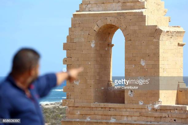 A man points towards a bulletridden wall in the historic town of Sabratha 40 kilometres west of Tripoli where the GNA is based on October 7 2017 A...
