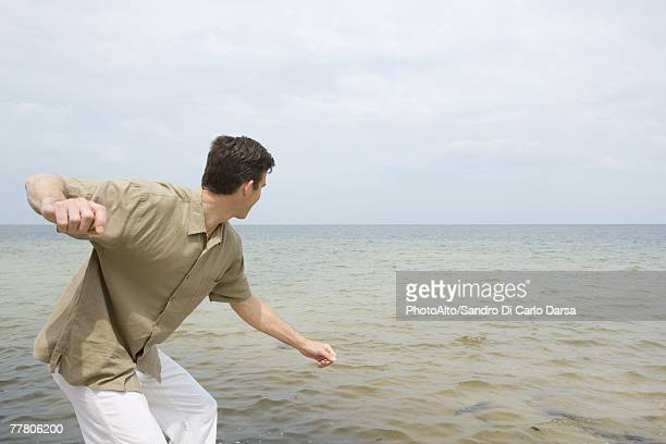 Man poised to skim stone on surface of ocean, side view, three quarter length
