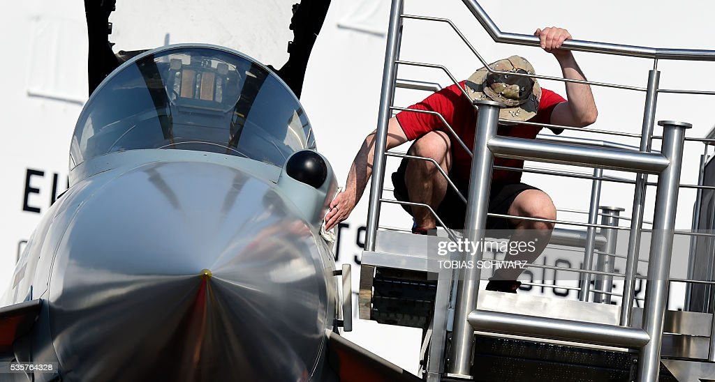 A man polishes a 'Eurofighter Typhoon' aircraft at the International Aerospace Exhibition (ILA) in Schoenefeld on May 30, 2016. The Aerospace Exhibition at Schoenefeld Airport takes place from June 1 to 4, 2016. / AFP / TOBIAS