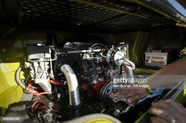 A man polishes his highly modified 1776cc engine in the back of his VW Baywindow Type 2 Transporter at Vanfest festival in the Three Counties...