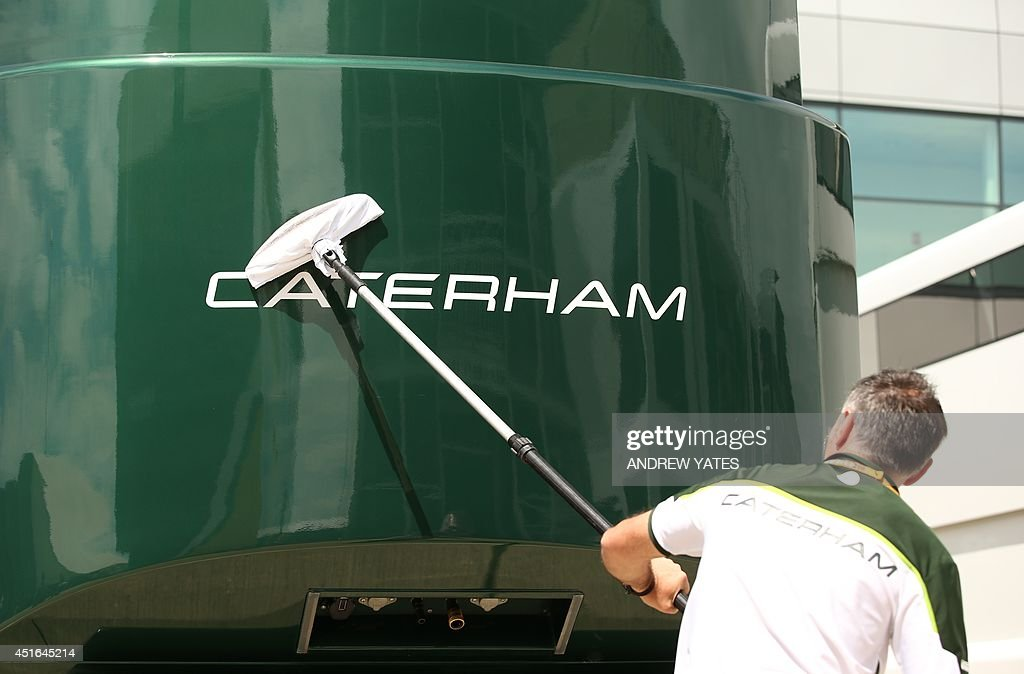 A man polishes the Caterham team motorhome in the paddock at the Silverstone circuit in Silverstone on July 3 2014 ahead of the British Formula One...
