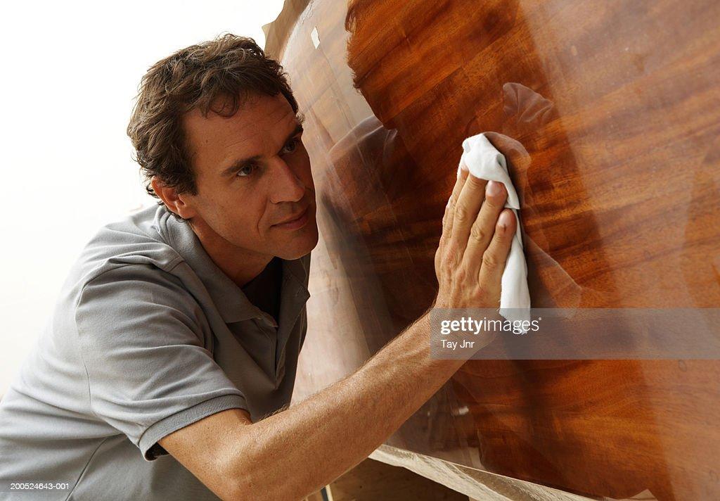 Man polishing boat in workshop : Stock Photo