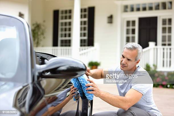 Man polishing car in front of house.