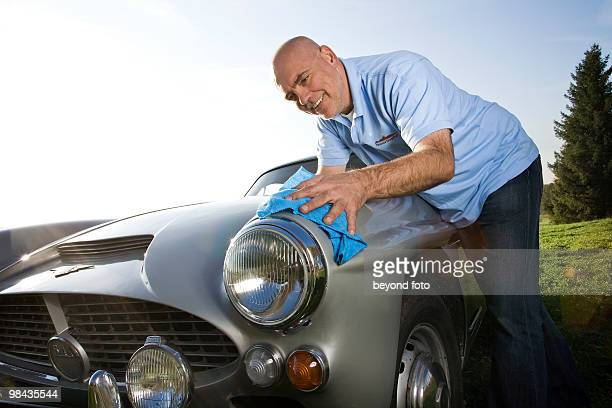 man polishing his classic car with cloth