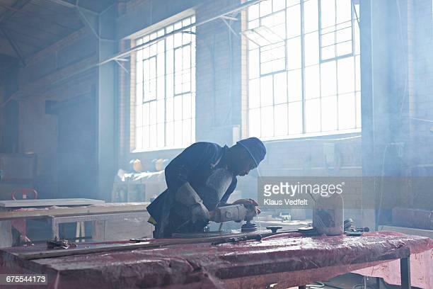 Man polishing marble slab at factory