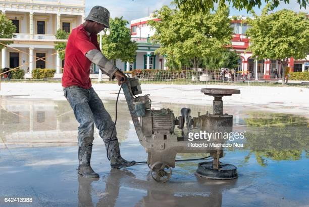 Man polishing the Calixto Garcia plaza granite floor with rustic homemade equipment Cuban real people lifestyle in the Caribbean Island