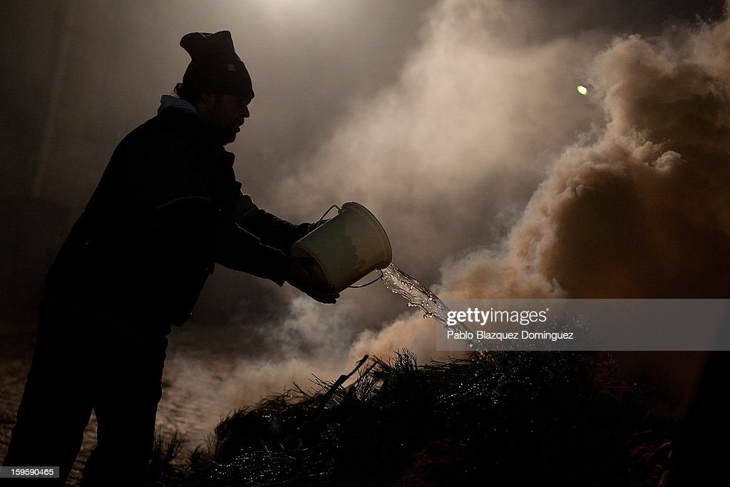 A man poors water over a bonfire on January 16, 2013 in San Bartolome de Pinares, Spain. In honor of San Anton, the patron saint of animals, horses are riden through the bonfires on the night before the official day of honoring animals in Spain.