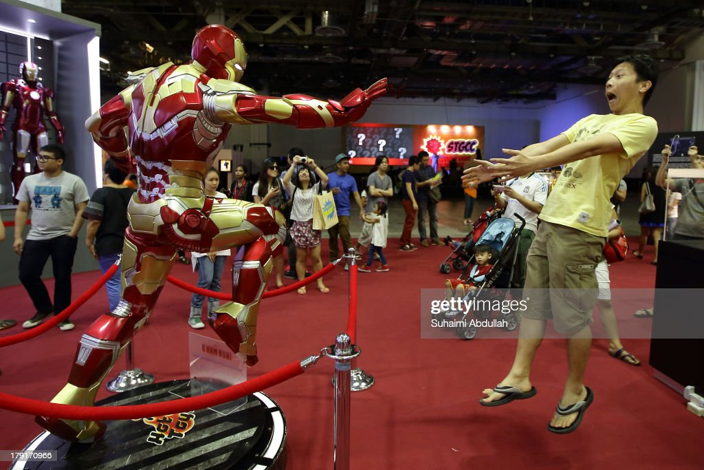 A man pose for a photo with a life size replica of Iron Man during the Singapore Toy, Game & Comic Convention (STGCC) at the Sands Expo & Convention Centre at Marina Bay Sands on September 01, 2013 in Singapore. The STGCC attracts thousands of fans who gather to enjoy exhibitions celebrating comics, gaming and movies from both Western and Asian cultures.