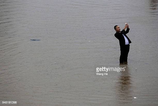 A man pose for pictures in the flooded at Wuhan £¬Hubei province China6 July 2016 An overnight storm following days of rain has stopped traffic cut...