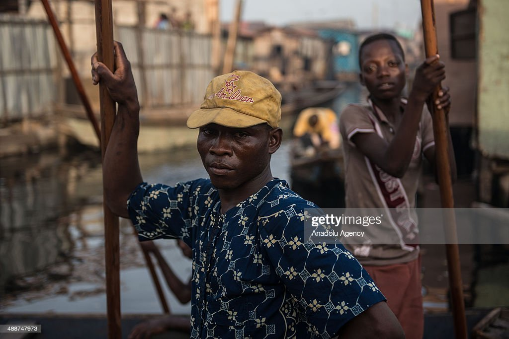 A man poses as canoes float past in the floating slum of Makoko on April 30, 2014 in Lagos, Negeria. Makoko is slum neighborhood located in Nigeria, its population considered to be thousands moreover the area was not officially counted. Makoko slum is seldom visited by anyone from outside.